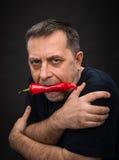Hombre mayor con la pimienta roja en su boca Imagenes de archivo