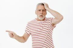 Retrato del hombre mayor en cuestión y confuso que es mano que se sostiene preocupada y preguntada derecha engañada en la cabeza foto de archivo