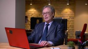 Retrato del hombre mayor en el traje formal que trabaja con el ordenador portátil que está atento y cansado en oficina almacen de video