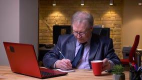 Retrato del hombre mayor en traje formal que mecanografía en el ordenador portátil y que escribe notas en el cuaderno que es conc metrajes