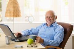 Retrato del hombre mayor feliz con el ordenador imagenes de archivo