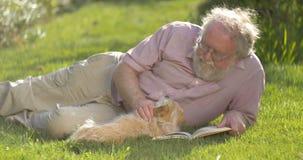 Retrato del hombre mayor jubilado que se relaja al aire libre leyendo un libro con el perro almacen de metraje de vídeo