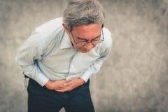 Retrato del hombre mayor que lleva a cabo sus manos en el estómago de dolor foto de archivo