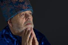 Retrato del hombre mayor que lleva la ropa oriental azul que mira para arriba contra fondo oscuro Imagen de archivo