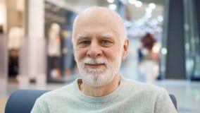 Retrato del hombre mayor que se sienta en la alameda que mira la cámara Comprador masculino en el centro comercial, sonriendo almacen de metraje de vídeo