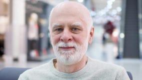 Retrato del hombre mayor sonriente hermoso que se sienta en alameda de compras El esperar masculino jubilado del comprador almacen de video