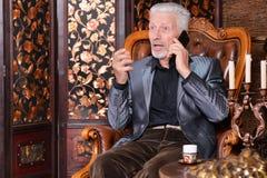Retrato del hombre mayor sonriente que habla en el tel?fono foto de archivo libre de regalías