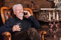 Retrato del hombre mayor sonriente que habla en el tel?fono imagen de archivo libre de regalías
