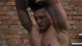 Retrato del hombre muscular atractivo que saca un top sin mangas gris, camisa metrajes