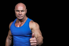 Retrato del hombre muscular confiado que muestra los pulgares para arriba Fotografía de archivo libre de regalías