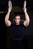 Retrato del hombre muscular del ajuste de los jóvenes que usa los anillos gimnásticos Imágenes de archivo libres de regalías