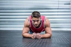 Retrato del hombre muscular en la posición del tablón Fotos de archivo libres de regalías