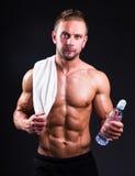 Retrato del hombre muscular joven que se coloca sobre gris con la toalla y Imagen de archivo