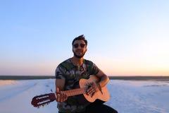 Retrato del hombre musulmán joven que juega música en la guitarra entre el san fotos de archivo