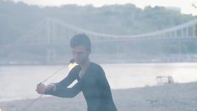 Retrato del hombre profesional que realiza una demostración con la situación de la fan del fuego en riverbank delante de árboles  almacen de metraje de vídeo