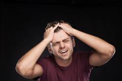 Retrato del hombre que lleva a cabo su cabeza en la tensión Imagen de archivo