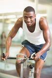 Retrato del hombre que se resuelve en la bicicleta estática en el gimnasio Imagenes de archivo