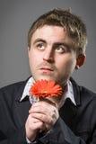 Retrato del hombre que sostiene la flor roja Fotografía de archivo libre de regalías