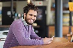Retrato del hombre que usa los teléfonos móviles mientras que se sienta en restaurante Fotografía de archivo