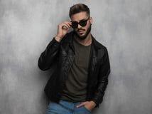 Retrato del hombre relajado atractivo en la chaqueta de cuero que arregla las gafas de sol foto de archivo