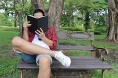 Retrato del hombre relajado joven que lee un libro en el banco en parque al aire libre hermoso Fotografía de archivo