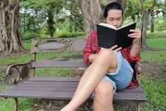 Retrato del hombre relajado joven que lee un libro en el banco en parque al aire libre hermoso Fotos de archivo libres de regalías