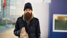 Retrato del hombre sin hogar borracho con alcohol de la bebida de la bolsa de papel mientras que se coloca en la calle de la ciud imagenes de archivo