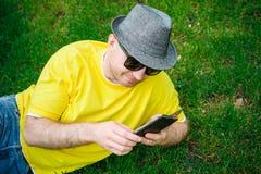 Retrato del hombre sonriente joven en el sombrero y los vidrios que se sientan en hierba verde con el teléfono Fotos de archivo libres de regalías