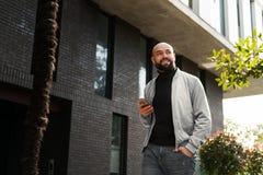 Retrato del hombre sonriente joven usando smartphone en la calle de la ciudad El hombre env?a el mensaje de texto lifestyle Redes fotos de archivo libres de regalías