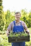 Retrato del hombre sonriente que celebra el cajón de plantas en conserva en el jardín Imagen de archivo libre de regalías