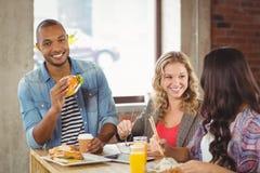 Retrato del hombre sonriente que come la hamburguesa con los colegas Imagen de archivo