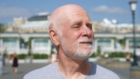 Retrato del hombre sonriente que se coloca al aire libre de mirada de la cámara Pensionista que viaja en Moscú, Rusia almacen de video