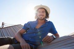 Retrato del hombre sonriente que se relaja en la hamaca en la playa Fotografía de archivo