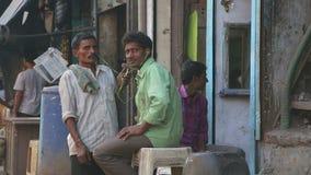 Retrato del hombre tres que se sienta en la calle en Bombay, primer almacen de video