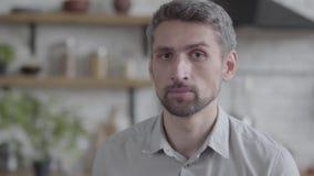 Retrato del hombre triste adulto que mira en la cámara y que intenta sonreír con la situación forzada de la sonrisa en la cocina  almacen de metraje de vídeo