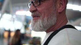 Retrato del hombre turístico mayor gris-barbudo que gandulea alrededor el aeropuerto El viajero lleva vidrios y un suéter blanco almacen de video