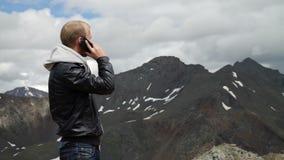 Retrato del hombre valeroso con una mochila que se sienta al borde de roca, pareciendo ausente y hablando en el teléfono en metrajes