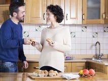 Retrato del hombre y de la mujer que comen los dulces hechos en casa en la cocina Imágenes de archivo libres de regalías
