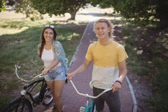 Retrato del hombre y de la mujer sonrientes que se colocan con la bicicleta Imagen de archivo