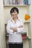 Retrato del housecleaner femenino que sostiene el plumero de la pluma Imagen de archivo libre de regalías