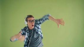 Retrato del inconformista alegre que escucha la música en los auriculares que bailan divirtiéndose almacen de metraje de vídeo