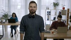 Retrato del inconformista joven con la barba en el lugar de trabajo almacen de video
