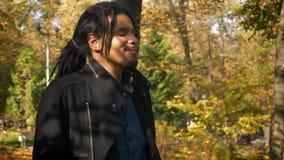 Retrato del individuo afroamericano con los dreadlocks que camina alrededor de parque otoñal almacen de video