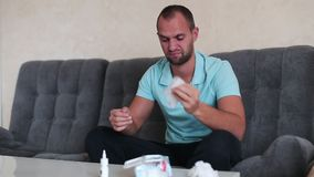 Retrato del individuo atractivo con un espray nasal y del tejido en manos, usando descensos de nariz, concepto de tratamiento par metrajes