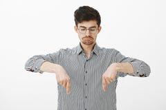 Retrato del individuo barbudo atractivo tranquilo contento en camisa rayada, señalando y mirando abajo con la expresión triste me Imagen de archivo libre de regalías