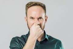 Retrato del individuo, cubriendo la nariz con los fingeres sobre fondo gris foto de archivo libre de regalías