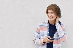 Retrato del individuo de moda con la camisa que lleva del peinado elegante que lleva a cabo mensajería del smartphone redes socia Fotos de archivo libres de regalías