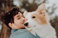 Retrato del individuo de risa y sonriente lindo alegre en ropa de los vaqueros con rojo del border collie del perro en sus manos  fotos de archivo libres de regalías