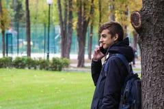 Retrato del individuo de Tenager con un teléfono que habla del smartphone Parque al aire libre Fotografía de archivo libre de regalías