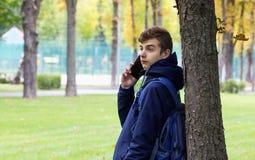 Retrato del individuo de Tenager con un teléfono que habla del smartphone Parque al aire libre Foto de archivo